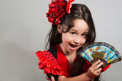 Cute little girl wearing beautiful red and black dress with matching head band, posing for camera using chinese hand fan. Studio background Stock Image