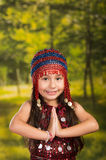 Cute little girl wearing beautiful red dress with matching pearl hat, posing for camera, green forest background Stock Photo