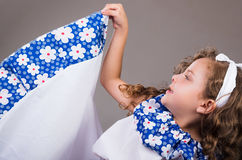 Cute little girl wearing beautiful white and blue dress with matching head band, actively posing for camera, studio Royalty Free Stock Photo