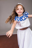 Cute little girl wearing beautiful white and blue dress with matching head band, actively posing for camera, studio Royalty Free Stock Images