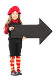 Cute little girl wearing beret and holding big arrow pointing ri. Full length portrait of a cute little girl wearing red beret and holding big black arrow stock photo
