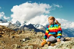 Child hiking in mountains. Cute little girl wearing bright rainbow colored coat and beige boots, resting in mountains, Switzerland Stock Photo