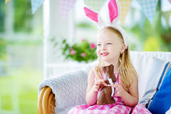 Cute little girl wearing bunny ears eating chocolate Easter rabbit Stock Photos