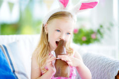 Cute little girl wearing bunny ears eating chocolate Easter rabbit Stock Image