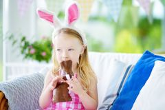 Cute little girl wearing bunny ears eating chocolate Easter rabbit Royalty Free Stock Photo