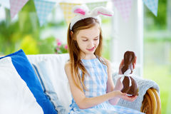 Cute little girl wearing bunny ears eating chocolate Easter rabbit Stock Photography