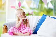 Cute little girl wearing bunny ears eating chocolate Easter rabbit. Kid playing egg hunt on Easter. Royalty Free Stock Image