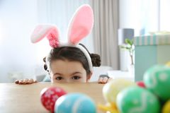 Cute little girl wearing bunny ears headband hiding behind table with painted Easter eggs royalty free stock photography