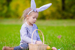 Cute little girl wearing bunny ears playing with Easter eggs on spring day outdoors Stock Photography