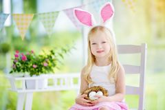 Cute little girl wearing bunny ears playing egg hunt on Easter Royalty Free Stock Images