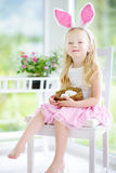 Cute little girl wearing bunny ears playing egg hunt on Easter Royalty Free Stock Image