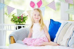 Cute little girl wearing bunny ears playing egg hunt on Easter Royalty Free Stock Photo