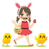 Girl Easter Chicks. Cute little girl wearing bunny headband with basket full of colorful chocolate eggs and chicks friends on Easter day Royalty Free Stock Photo