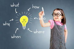 Cute little girl wearing business dress and analyzing problem and find solution. Blue background. Stock Photo