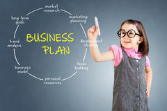 Cute little girl wearing business dress and drawing business plan concept. Blue background. Stock Image