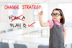 Cute little girl wearing business dress and drawing business plan strategy changing. Office background. Stock Photography