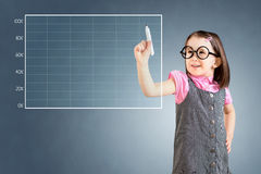 Cute little girl wearing business dress and drawing on empty graph. Blue background. Stock Photo