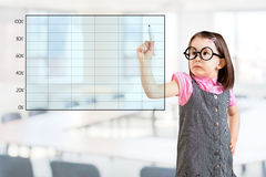 Cute little girl wearing business dress and drawing on empty graph. Office background. Royalty Free Stock Image