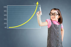 Cute little girl wearing business dress and drawing over target achievement graph. Blue background. Royalty Free Stock Photo