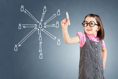 Cute little girl wearing business dress and drawing social network structure. Blue background. Stock Photography