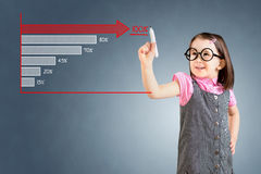 Cute little girl wearing business dress and drawing a stock chart. Blue background. Stock Photography
