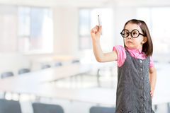Cute little girl wearing business dress and draws something on virtual screen. Office background. Royalty Free Stock Photos