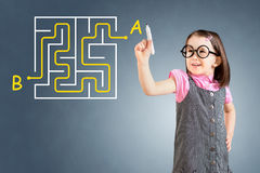 Cute little girl wearing business dress and finding the maze solution writing on the whiteboard. Blue background. Cute little girl wearing business dress and royalty free stock photo
