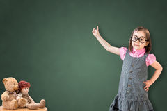 Cute little girl wearing business dress and show something on green chalk board. Royalty Free Stock Photo
