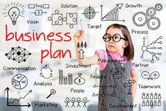 Cute little girl wearing business dress and writing business plan concept. Office background. Royalty Free Stock Photos