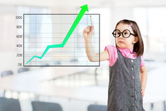 Cute little girl wearing business dress and writing over achievement graph. Office background. Royalty Free Stock Photo