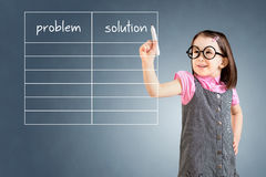 Cute little girl wearing business dress and writing problem and solution list in blank. Blue background. Royalty Free Stock Photography