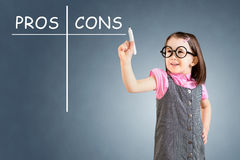 Cute little girl wearing business dress and writing pros and cons comparison concept. Blue background. Stock Photos