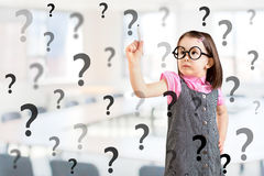 Cute little girl wearing business dress and writing question mark. Office background. Royalty Free Stock Image