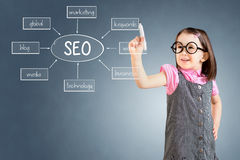 Cute little girl wearing business dress and writing a SEO schema on the whiteboard. Blue background. Stock Image
