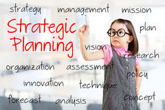 Cute little girl wearing business dress and writing strategic planning concept. Office background. Stock Photos