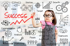 Cute little girl wearing business dress and writing success by many process. Office background. Stock Images