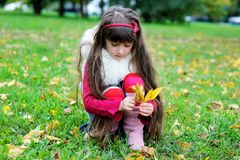 Cute little girl wearing fur coat in autumn forest Royalty Free Stock Image
