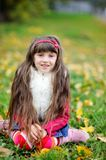 Cute little girl wearing fur coat in autumn forest Stock Images