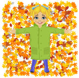Cute little girl wearing green raincoat lying on colorful autumn leaves in park. Cute little girl wearing green raincoat lying on colorful autumn leaves in the Stock Image