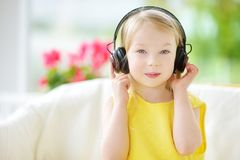 Cute little girl wearing huge wireless headphones. Pretty child listening to the music. Schoolgirl having fun listening to kid`s. Songs at home. Home Stock Photography