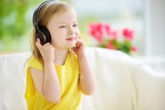 Cute little girl wearing huge wireless headphones. Pretty child listening to the music. Schoolgirl having fun listening to kid`s. Songs at home. Home Royalty Free Stock Photo