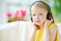 Cute little girl wearing huge wireless headphones. Pretty child listening to the music. Schoolgirl having fun listening to kid`s. Songs at home. Home Stock Image