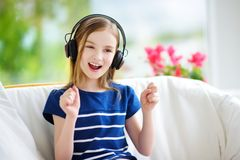 Cute little girl wearing huge wireless headphones. Pretty child listening to the music. Schoolgirl having fun listening to kid`s. Songs at home. Home Stock Photo