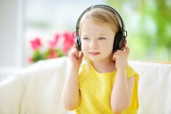 Cute little girl wearing huge wireless headphones. Pretty child listening to the music. Schoolgirl having fun listening to kid`s. Songs at home. Home Stock Photos