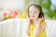 Cute little girl wearing huge wireless headphones. Pretty child listening to the music. Schoolgirl having fun listening to kid`s. Songs at home. Home Stock Images