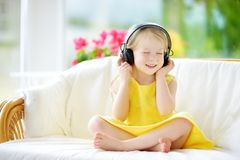 Cute little girl wearing huge wireless headphones. Pretty child listening to the music. Schoolgirl having fun listening to kid`s. Songs at home. Home Royalty Free Stock Photography