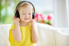 Cute little girl wearing huge wireless headphones. Pretty child listening to the music. Schoolgirl having fun listening to kid`s Stock Photos