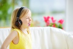 Cute little girl wearing huge wireless headphones. Pretty child listening to the music. Schoolgirl having fun listening to kid`s. Songs at home. Home Royalty Free Stock Images