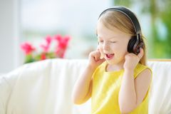 Cute little girl wearing huge wireless headphones. Pretty child listening to the music. Schoolgirl having fun listening to kid`s Stock Images
