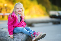 Cute little girl wearing jacket sitting on a tree log on beautiful sunny autumn day Royalty Free Stock Photos